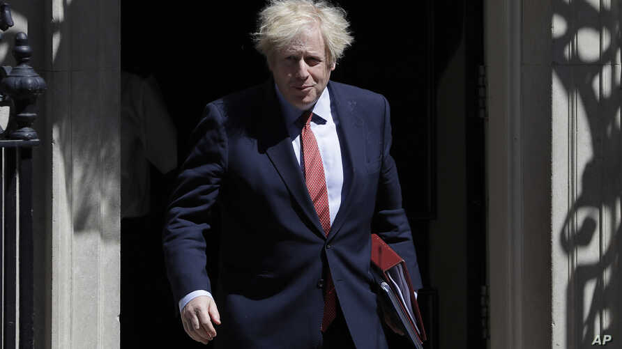 Britain's Prime Minister Boris Johnson leaves Downing Street to attend the weekly session of PMQs in Parliament in London as…
