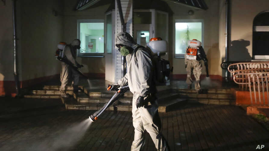 Servicemen of Belarus Ministry of Defence wearing protective gear disinfect a local hospital in the town of Zaslavl, outside…