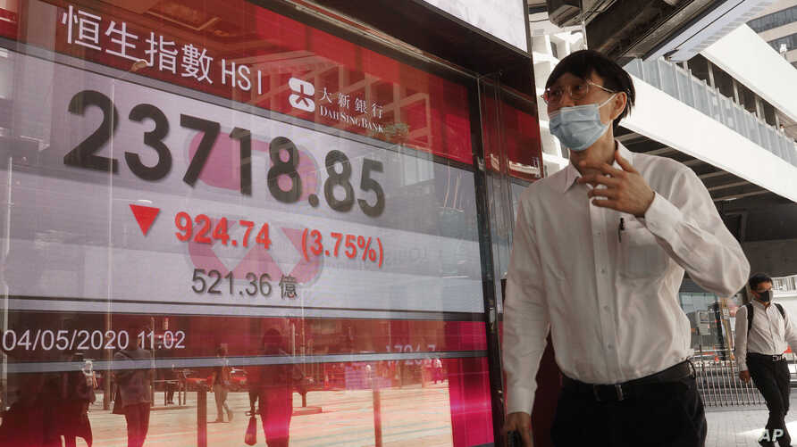 A man wearing face mask walks past a bank electronic board showing the Hong Kong share index at Hong Kong Stock Exchange Monday…
