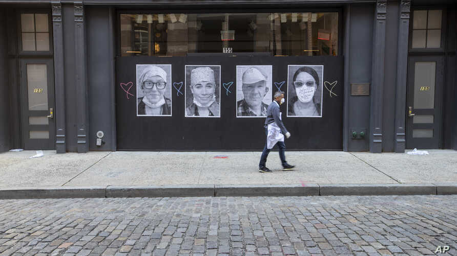 A man wearing a face mask to protect against the coronavirus walks past a closed Dolce & Gabbana store, Thursday, May 7, 2020,…