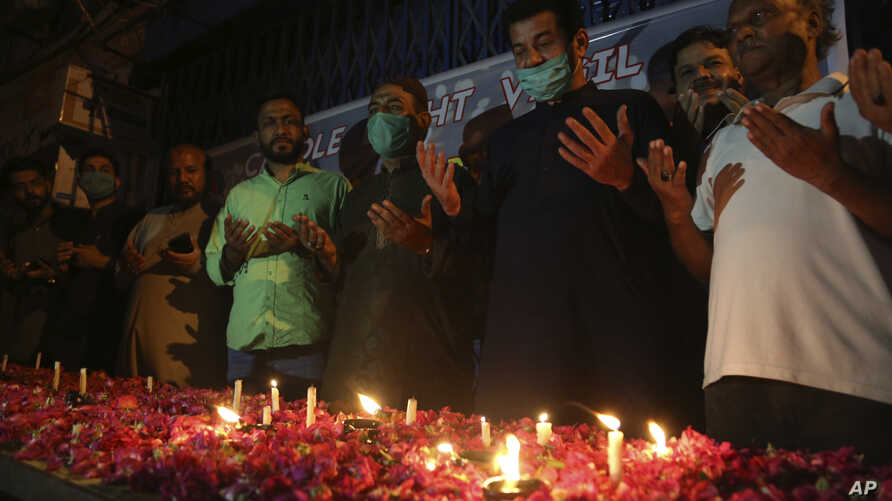 People attend candlelight vigil for victims of the crash of a state-run Pakistan International Airlines plane on Friday, in…