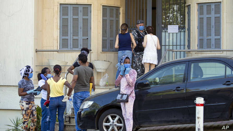 In this Thursday, May 21, 2020 photo, Ethiopian workers wait outside the Ethiopian Consulate in Hazmieh, east of Beirut,…