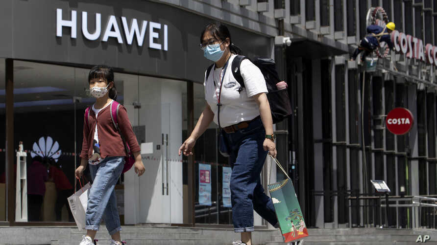 Residents wearing face masks to protect against the coronavirus walk past a Huawei retail store in Beijing on Monday, May 18,…