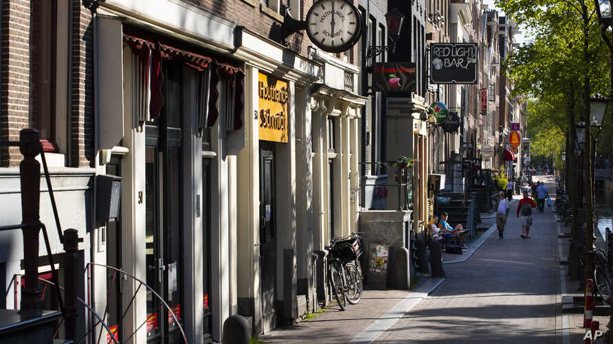 Sex workers booths, sex shows, clubs, movie theaters, and stores are closed in a near-deserted Red Light District, Amsterdam,…