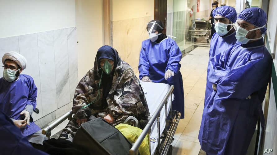 FILE - In this March 7, 2020 file photo, a patient infected with the new coronavirus is moved, at Baqiyatallah Al'Azam Hospital…
