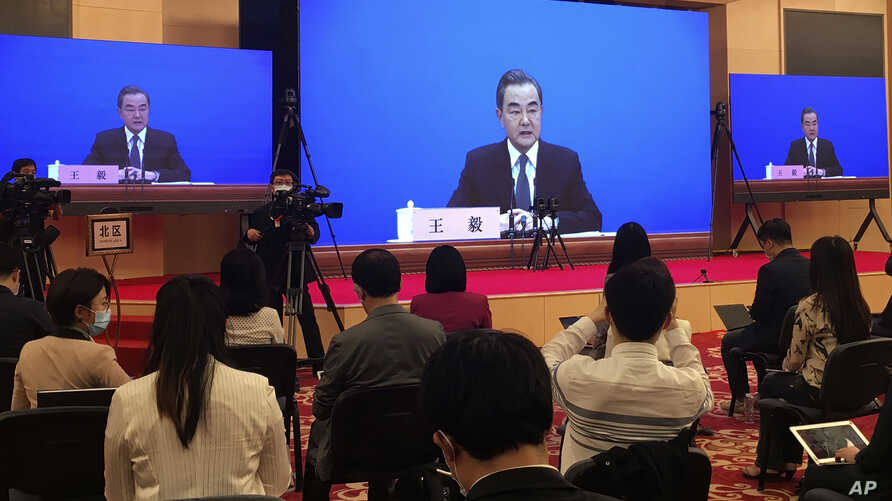 FILE - In this Sunday, May 24, 2020, file photo, China's Foreign Minister Wang Yi is seen broadcasted remotely on big screens…