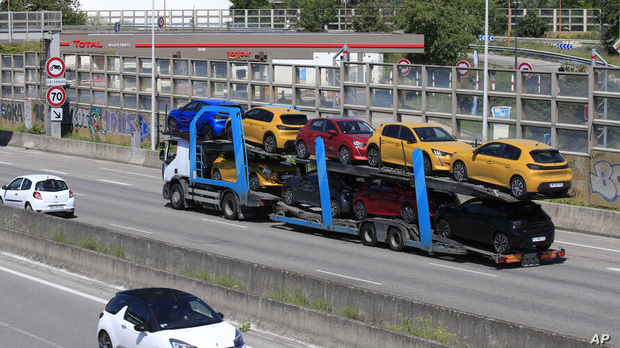 A truck carries new cars on the motorway leading to Paris, Tuesday, May 26, 2020 in Villacoublay, west of Paris. French…