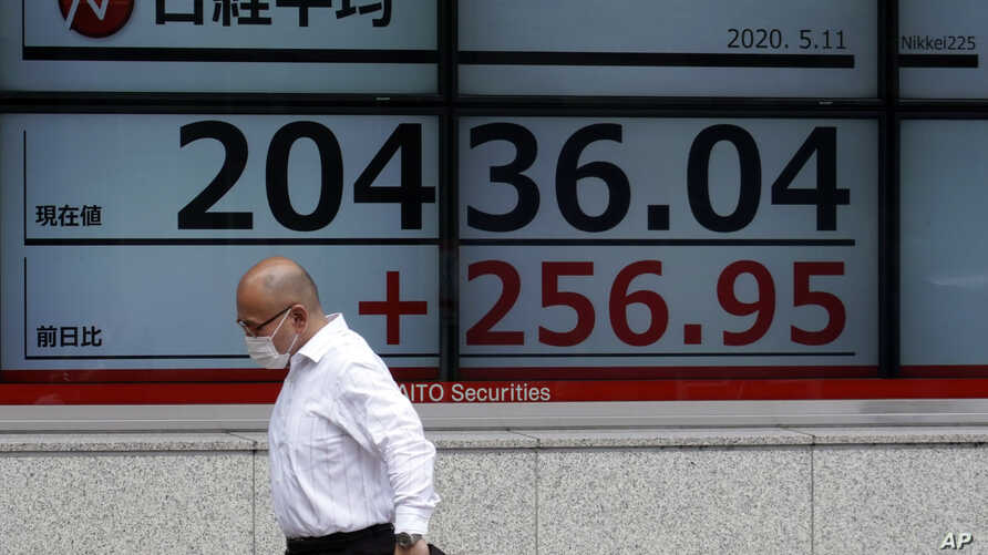 A man wearing a face mask  walks past an electronic stock board showing Japan's Nikkei 225 index at a securities firm in Tokyo…
