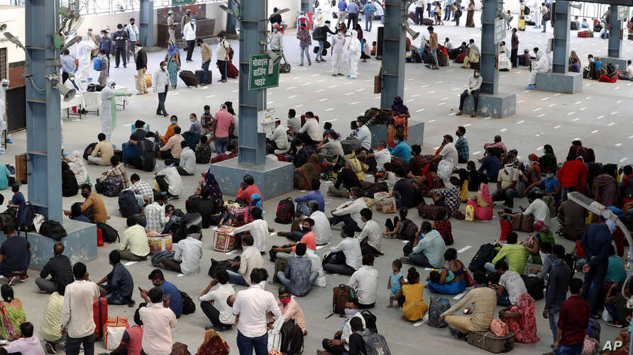 Migrant laborers, who arrived from Gujarat state on a train, rest before processding for their native villages in their home…