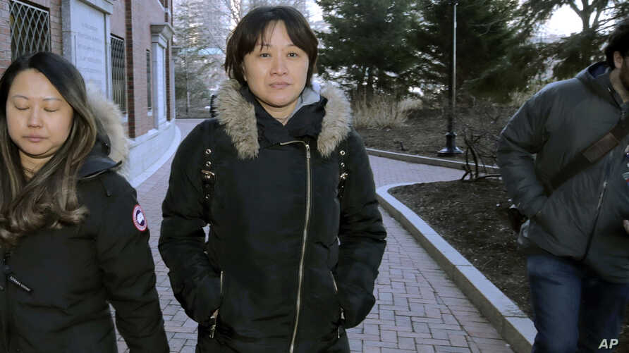 Xiaoning Sui, center, a Chinese national residing in British Columbia, Canada, leaves federal court, Friday, Feb. 21, 2020, in…