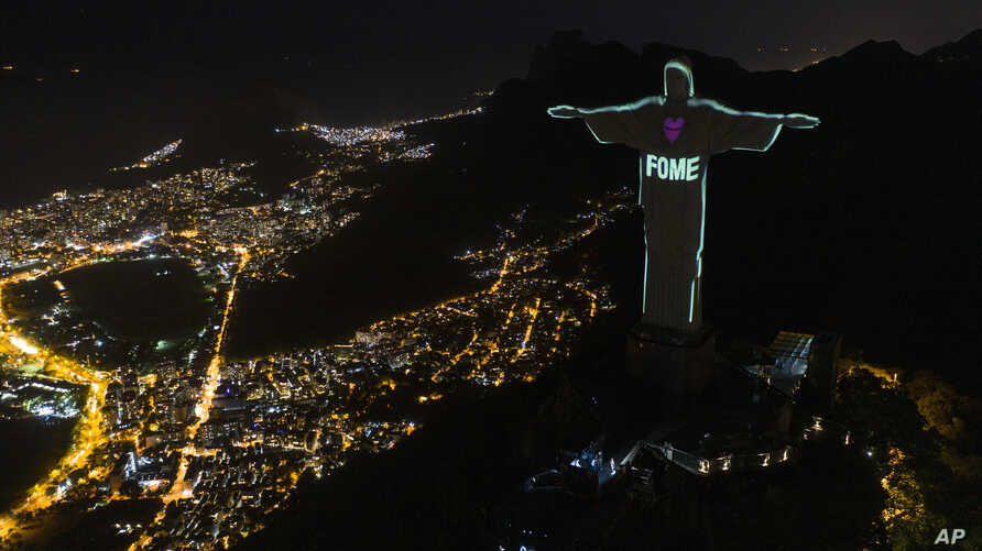 "The Portuguese word ""Hunger"" is projected over the Rio's Christ the Redeemer statue amid the new coronavirus outbreak in Rio de…"