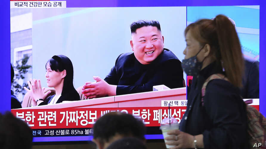 A woman passes by a TV screen showing an image of North Korean leader Kim Jong Un and his sister Kim Yo Jong during a news…