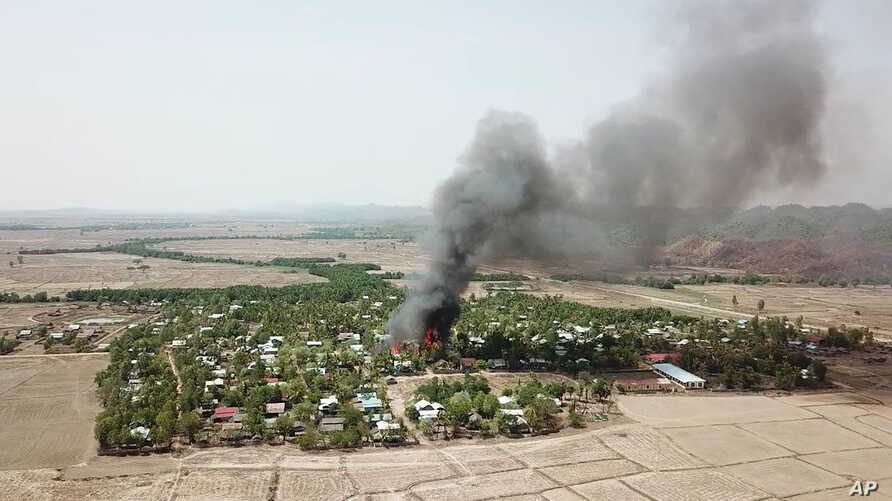 In this photo released by the Myanmar Army, a fire burns May 16, 2020, in the predominantly ethnic Rakhine village of Let Kar…