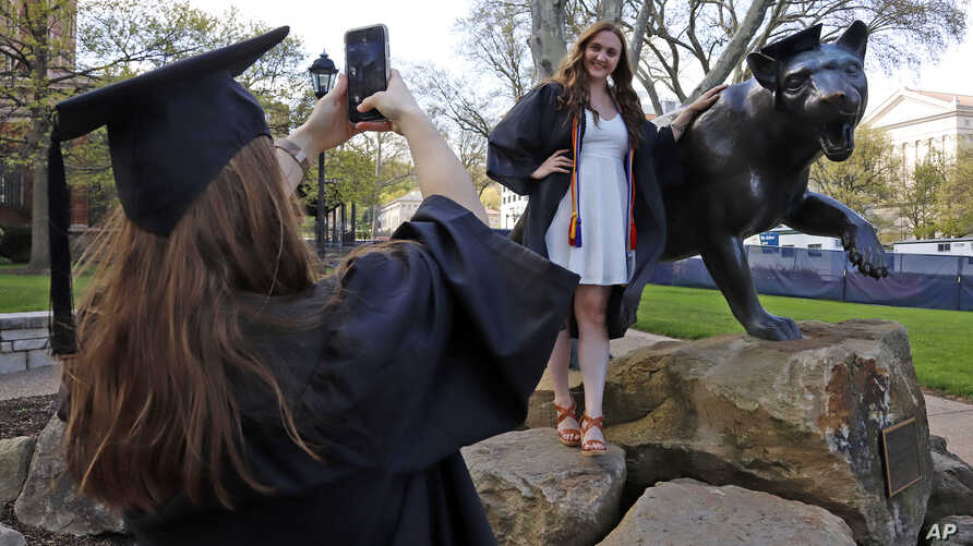 FILE - In this April 27, 2020, file photo, Class of 2020 University of Pittsburgh graduates Shannon Trombley, left, of…