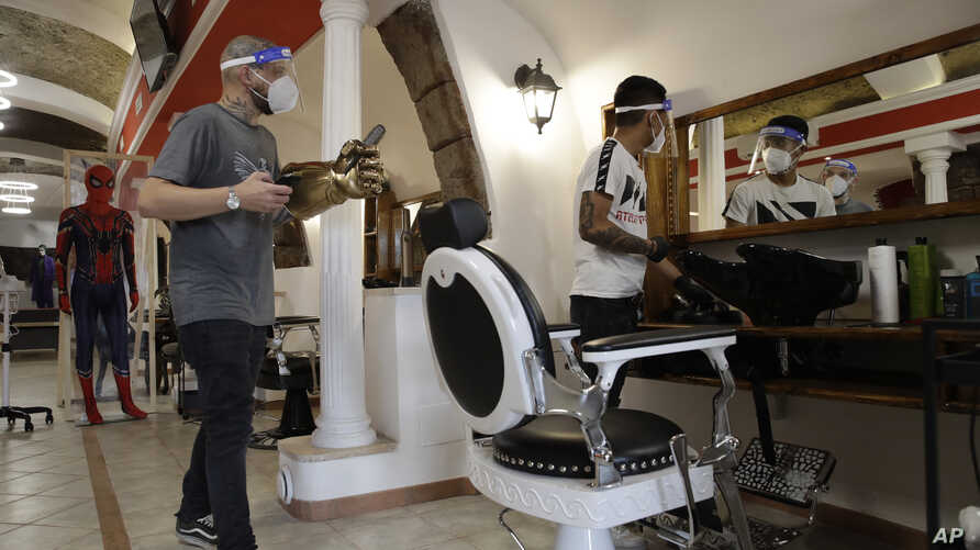 Workers wearing face masks to prevent the spread of COVID-19, prepare for the opening of the barber shop Bulli, in Rome,…