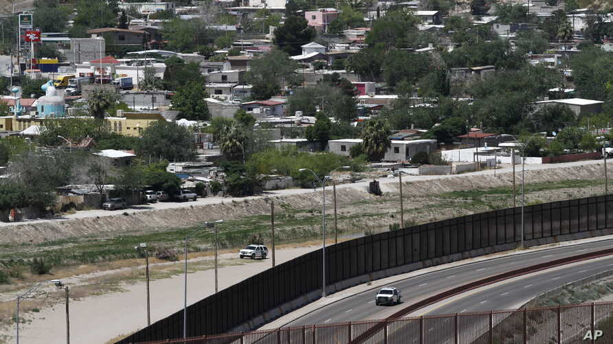 A residential neighborhood of Juarez, Mexico, and U.S. Border Patrol vehicles on both sides of a border fence as seen from El…