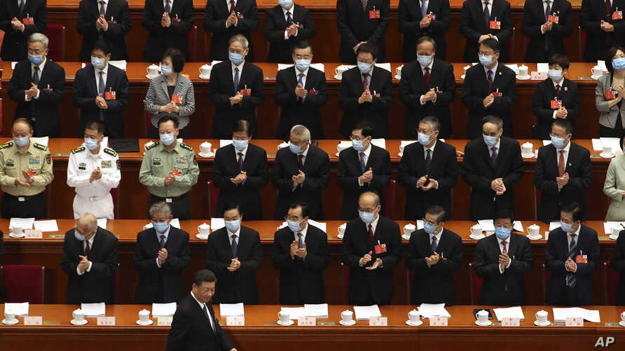 Delegates applaud as Chinese President Xi Jinping arrives for the opening session of China's National People's Congress (NPC)…