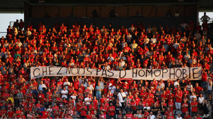 "FILE - In this Saturday, Aug. 31, 2019 file photo, Nimes fans hold up a banner that reads ""with us no homophobia"" before the…"