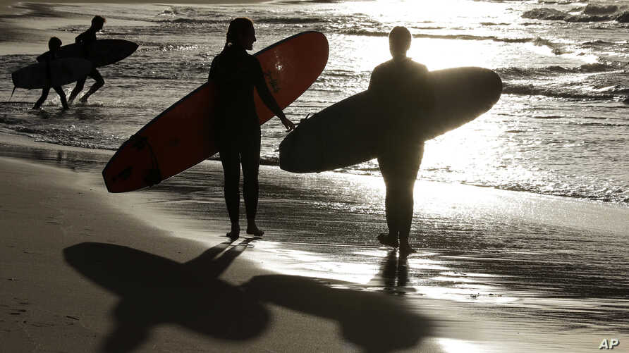 FILE - In this April 28, 2020, file photo, surfers walk along Bondi Beach in Sydney as coranavirus pandemic restrictions are…