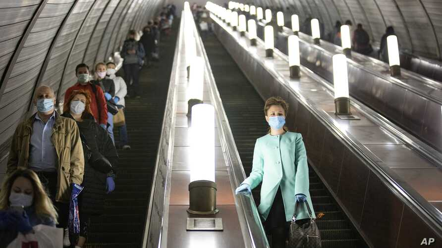 People wearing face masks and gloves to protect against coronavirus, observe social distancing guidelines as they go down the…