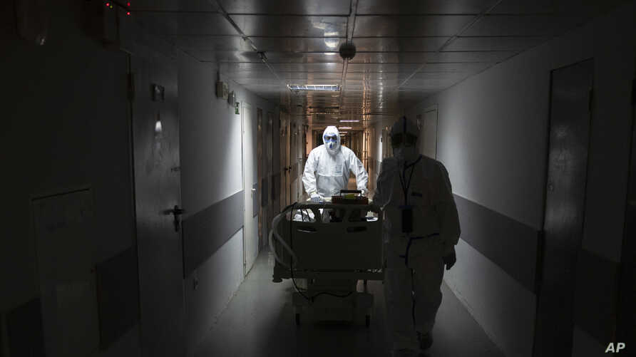 Medical workers move a coronavirus patient at an intensive care unit of the Filatov City Clinical Hospital in Moscow, Russia,…