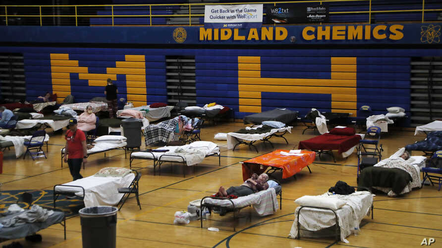 Volunteers assist evacuated Midland residents at a temporary shelter at Midland High School, Wednesday, May 20, 2020, in…