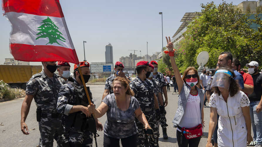 An anti-government protester yells as she and others block a main highway outside the Ministry of Energy and Water after…