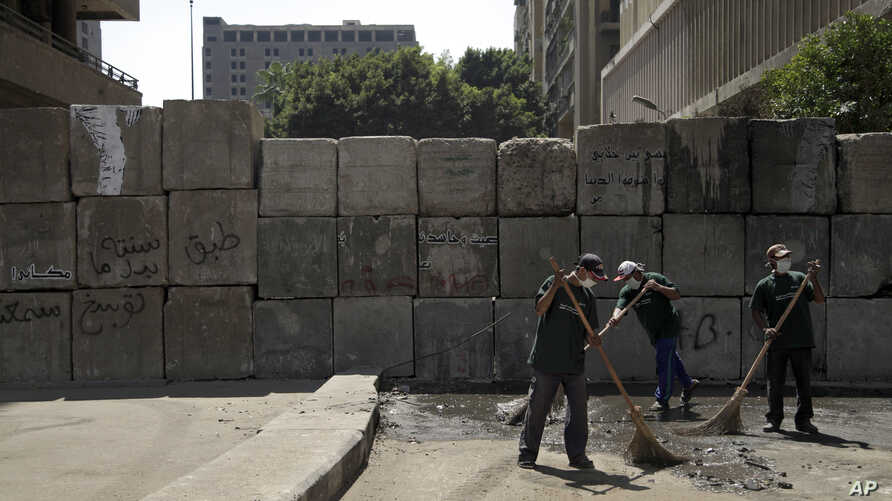 Egyptian street cleaners clean up the area around the U.S. embassy in Cairo, Egypt, Saturday, Sept. 15, 2012 after days of…