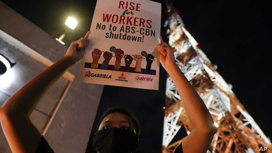 An activist holds a slogan outside the headquarters of broadcast network ABS-CBN corp. on Tuesday, May 5, 2020 in Quezon city,…