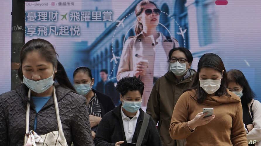 People wearing protective face masks walk on a street in the Central, the business district of Hong Kong, Tuesday, Feb. 11,…