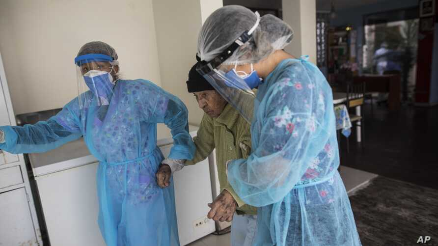 Nurses wearing protective gear walk with an elderly woman at the Mas Vida home for senior citizens, in Lima, Peru, Tuesday, May…