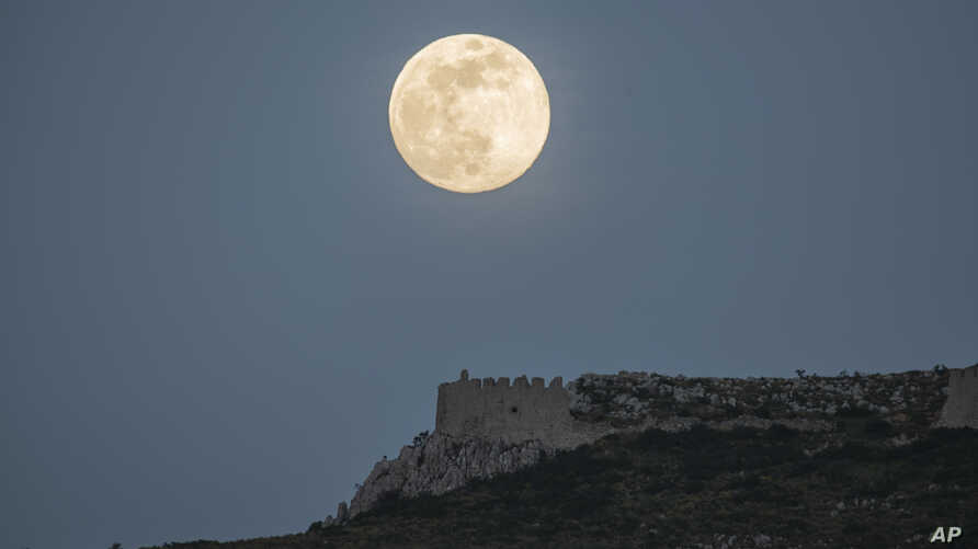 The moon rises above the castle of Acrocorinth, the acropolis of ancient Corinth, about 80 kilometers (50 miles) southwest of…