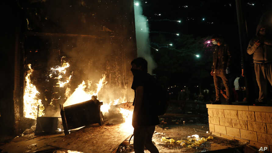 Protesters set fires at the 3rd Precinct of the Minneapolis Police Department, Thursday, May 28, 2020, in Minneapolis. Violent…