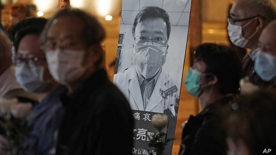 FILE - In this Feb. 7, 2020, file photo, people wearing masks attend a vigil for Chinese doctor Li Wenliang, who was…