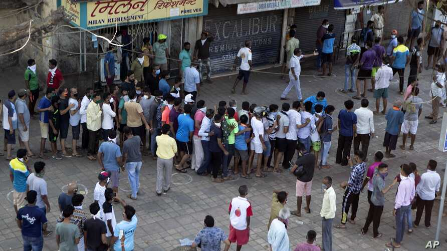 Indians line up without maintaining physical distance to buy liquor outside one of the liquor shops which reopened Monday after…