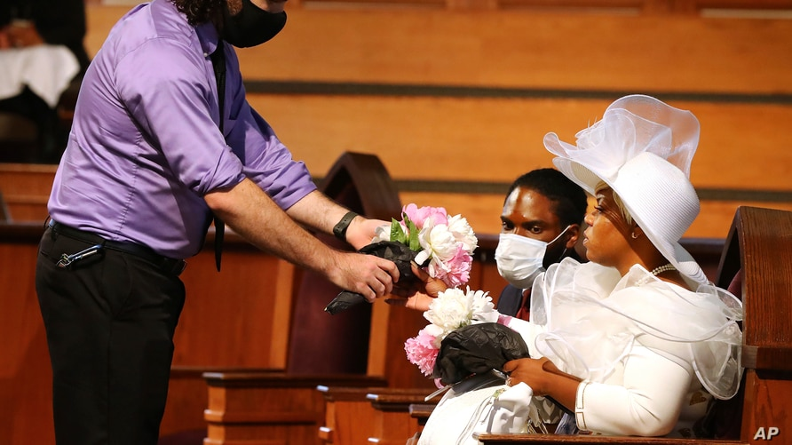 A mourner offers Tomika Miller, the wife of Rayshard Brooks, some flowers while attending his public viewing at Ebenezer…