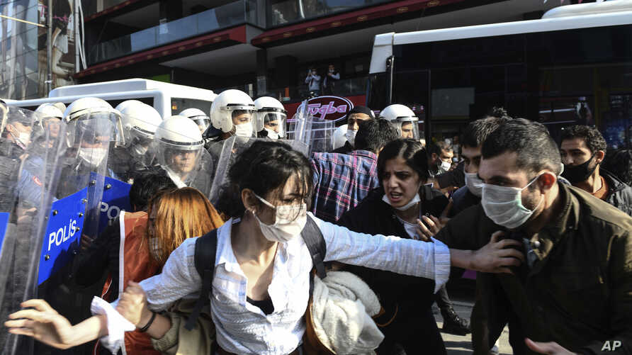 Turkish police officers, in riot gear, and wearing face masks for protections against the spread of the coronavirus, scuffle…