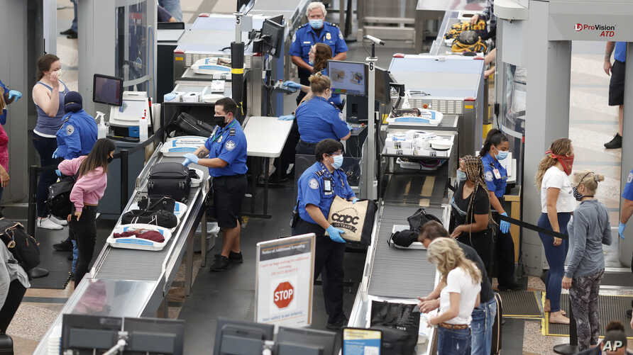 Transportation Security Administration agents process passengers at the south security checkpoint in Denver International…
