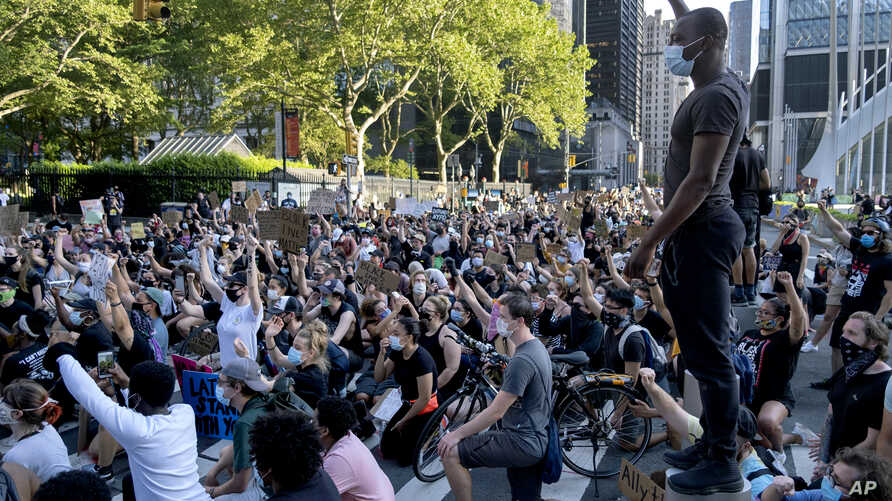 A group of protesters take a knee while marching in lower Manhattan, Saturday, June 6, 2020, in New York. Protests continued…