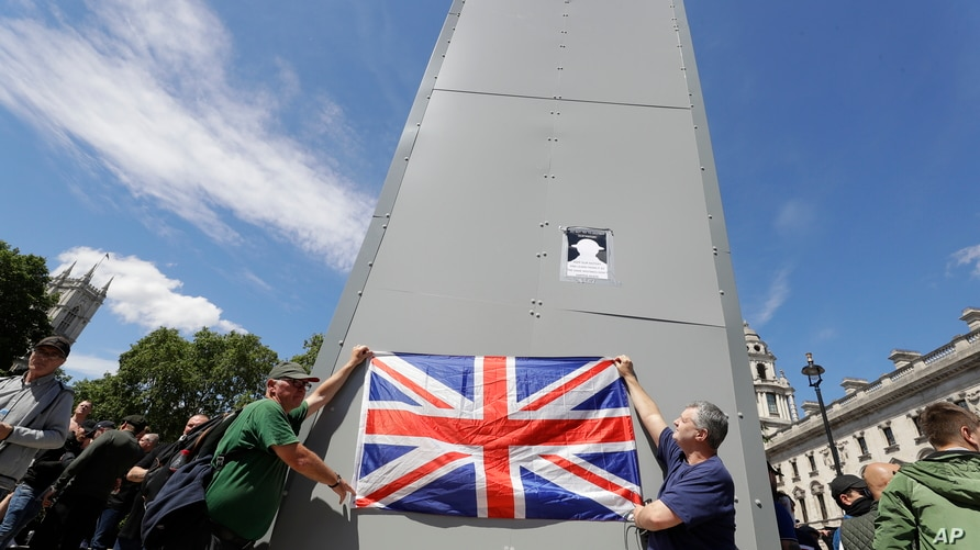 Members of far-right Football Lads Alliance hold a British flag in front of a protective covering surrounding the statue of…