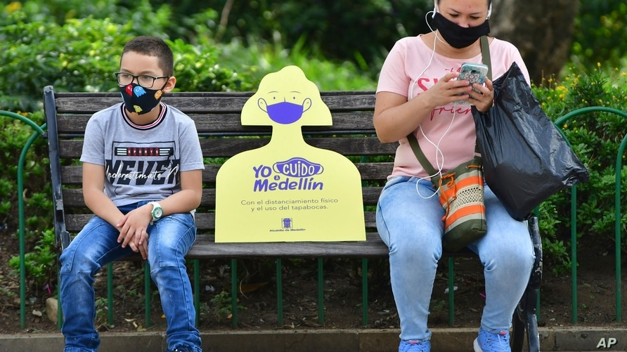 In this June 8, 2020 photo, a sign reminding citizens to maintain a safe social distance sits on a park bench between a woman…
