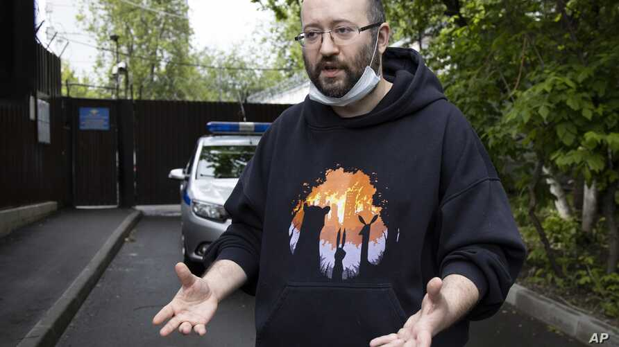 Prominent Russian journalist Ilya Azar, who was sentenced for holding a one-person protest amid lockdown, gestures while…