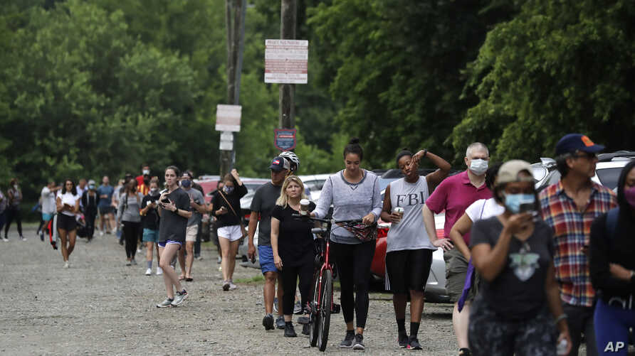People wait in line to vote in the Georgia's primary election at Park Tavern on Tuesday, June 9, 2020, in Atlanta. (AP Photo…