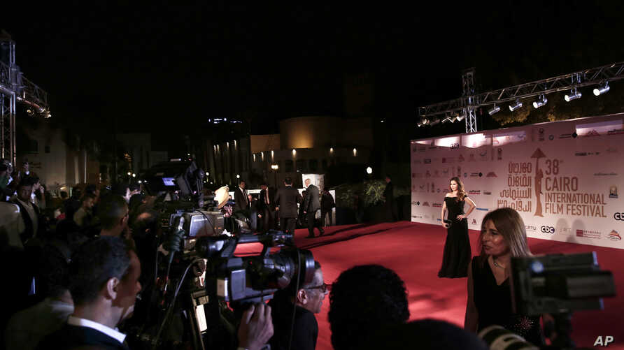 Photographers try to get attention of celebrities on the red carpet during the opening of the 38th Cairo International Film…