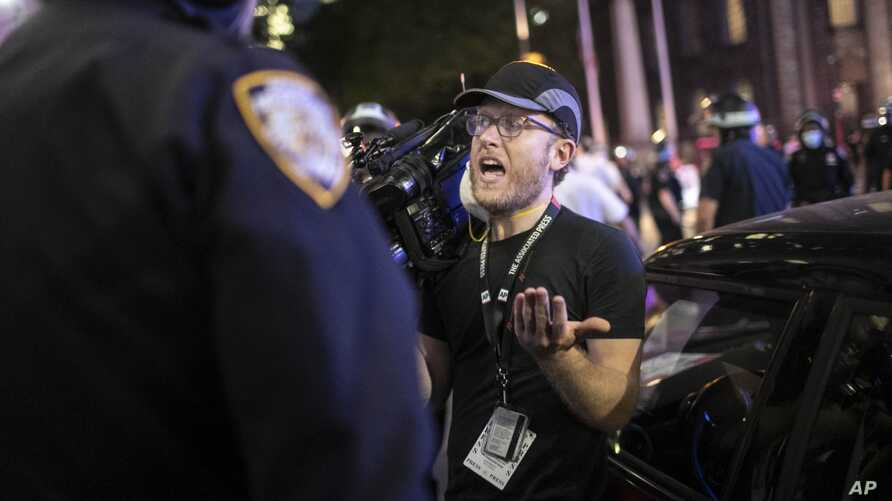 "Associated Press videojournalist Robert Bumsted reminds a police officer that the press are considered ""essential workers"" and…"