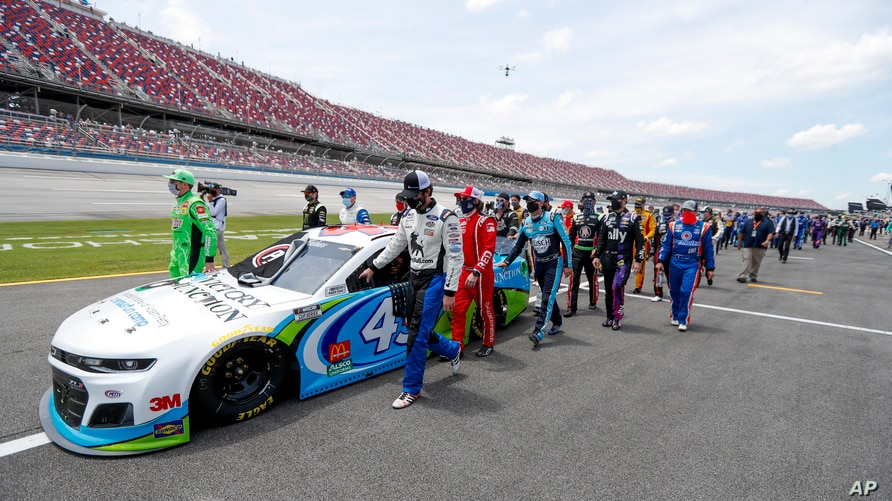 Nascar drivers Kyle Busch, left, and Corey LaJoie, right, join other drivers and crews as they push the car of Bubba Wallace to…