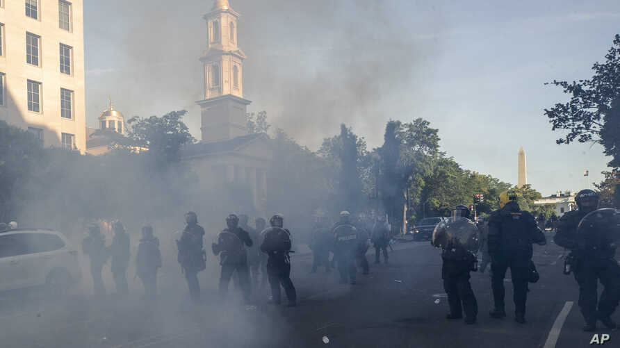 Tear gas floats in the air as a line of police move demonstrators away from St. John's Church across Lafayette Park from the…