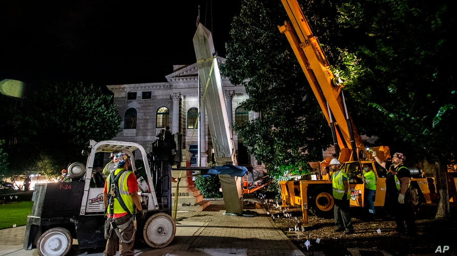 Workers remove a Confederate monument with a crane Thursday, June 18, 2020, in Decatur, Ga. The 30-foot obelisk in Decatur…