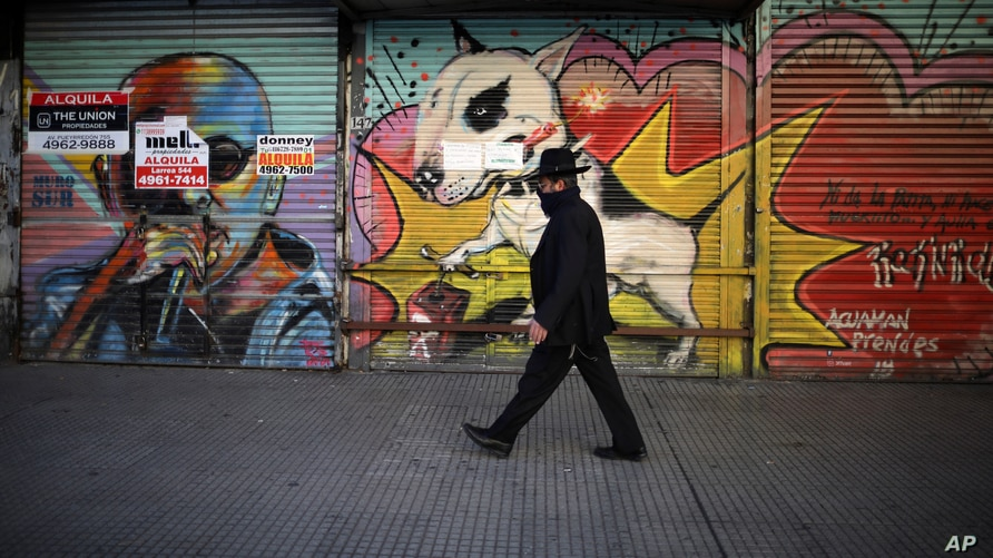 A man walks by a commercial area of closed shops during a government-ordered lockdown to curb the spread of the new coronavirus…