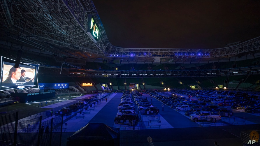 People watch a movie from inside their cars at a drive-in installed in the Palmeiras soccer stadium amid the coronavirus…